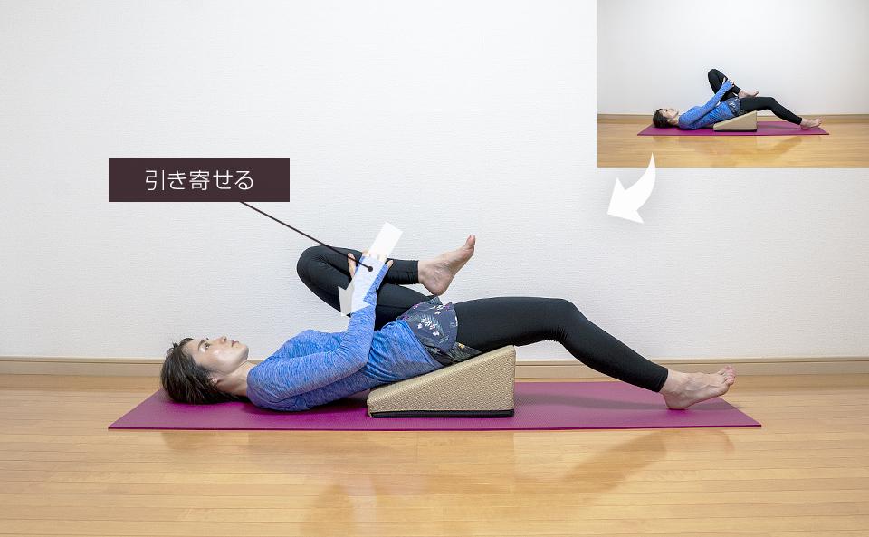 仰向けになり片脚を伸ばして逆脚を持ち上げて引き寄せるストレッチ