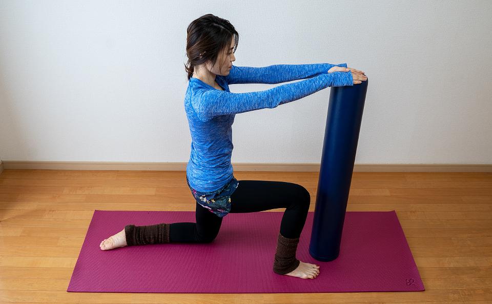 ストレッチポールを床に垂直に立て右膝を立てて左膝を床につく