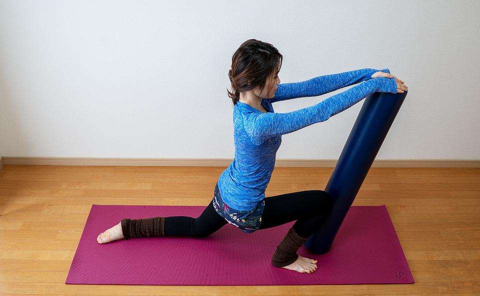 ストレッチポールを前に倒し左脚の太ももの付け根を伸ばす