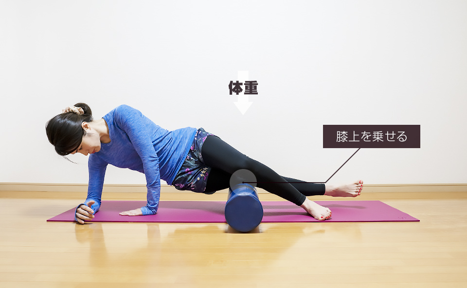 ストレッチポールに膝上の外側を乗せて体重をかけてほぐす