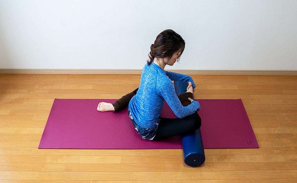 ストレッチポールの上に右脚の膝から下を乗せ左脚は後ろにおいて床に座る