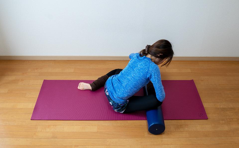 手をストレッチポールの両端におき背筋を伸ばしておしりが伸びるように前屈する