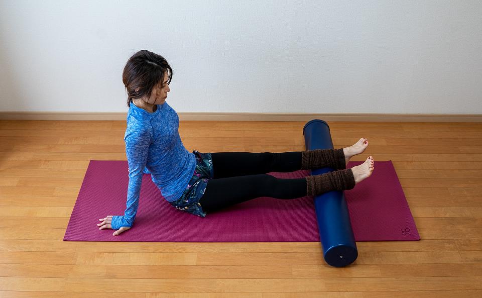 ふくらはぎをストレッチポールの上に乗せ腕を身体の横におき脚は肩幅に開く