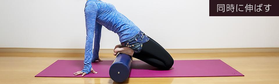 ストレッチポールに足の甲を乗せて両脚同時に太ももの前側を伸ばす