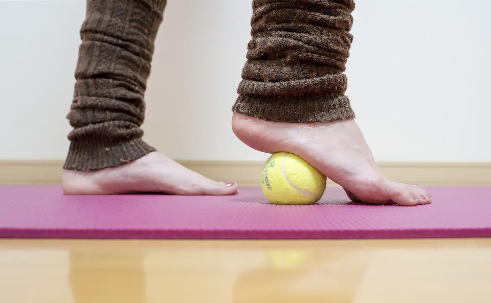 足裏のカカトの手前をテニスボールに乗せて体重をかけてほぐす