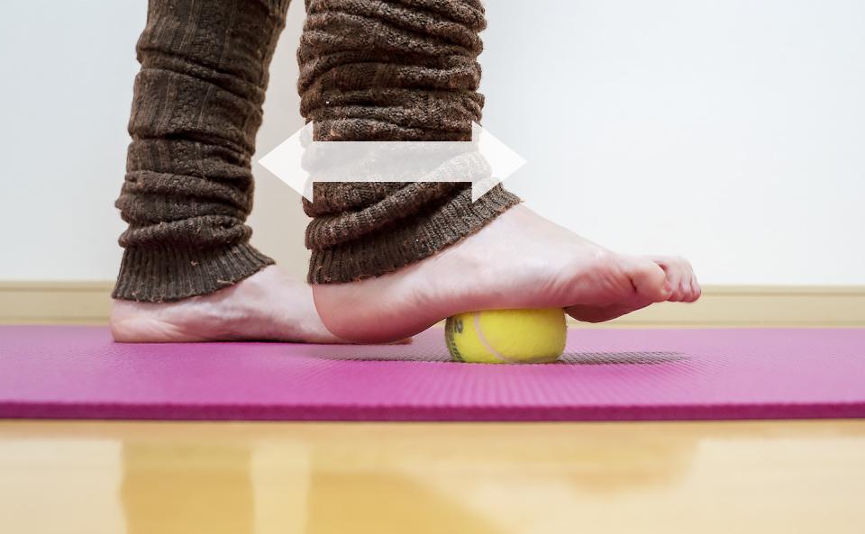足裏の土踏まず部分をテニスボールに乗せて体重をかけて前後に動かしてほぐす