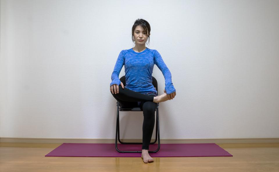 イスに座り右脚のすねを左脚の太ももに乗せる