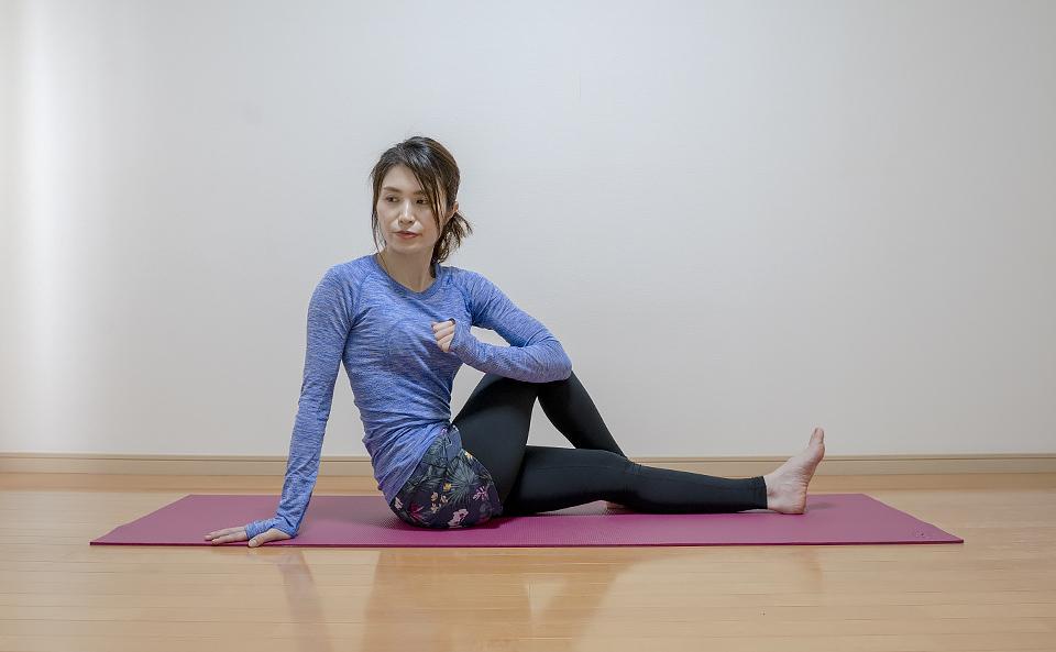 おしりの筋肉が伸びるように左ひじで右膝を押さえる