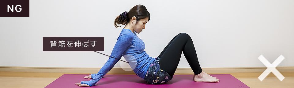 床に座って二の腕のストレッチのNG「背中が丸々と伸びづらいので注意」