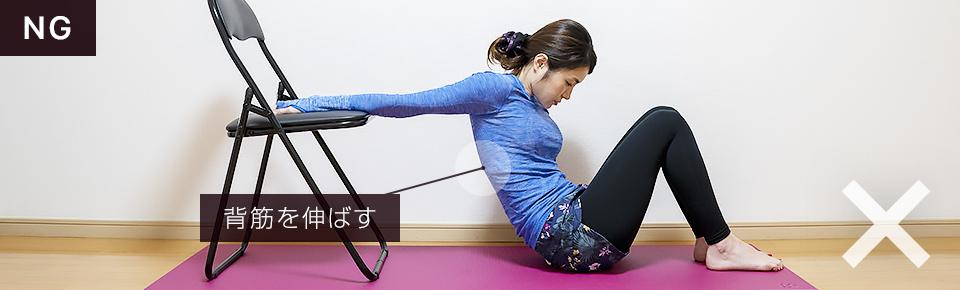 椅子を使って二の腕のストレッチのNG「背中が丸々と伸びづらいので注意」