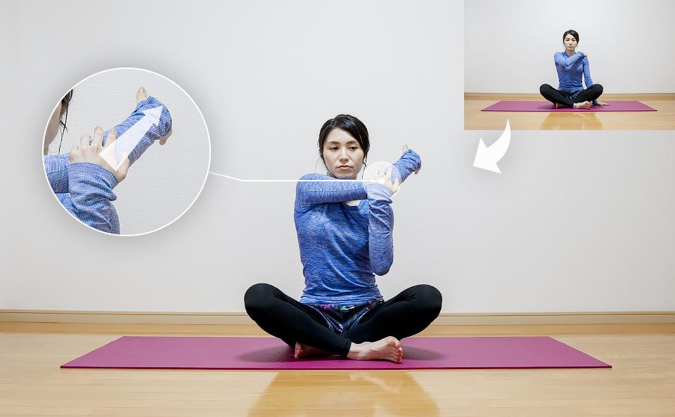 右の肩周りの筋肉が伸びるように手前に引き寄せる