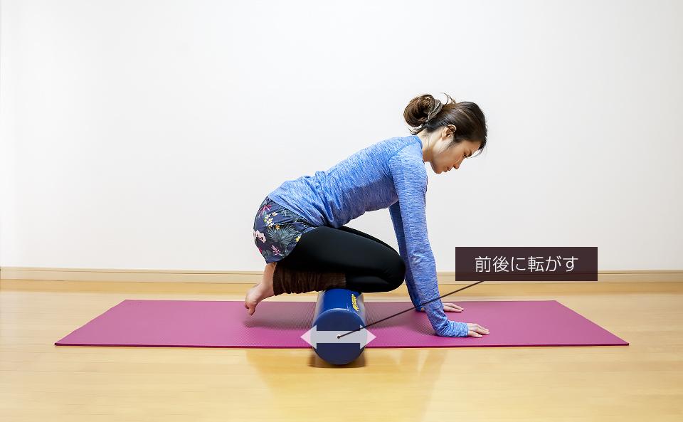 ストレッチポールにすねの筋肉を乗せて筋肉がほぐれるように前後に動かす