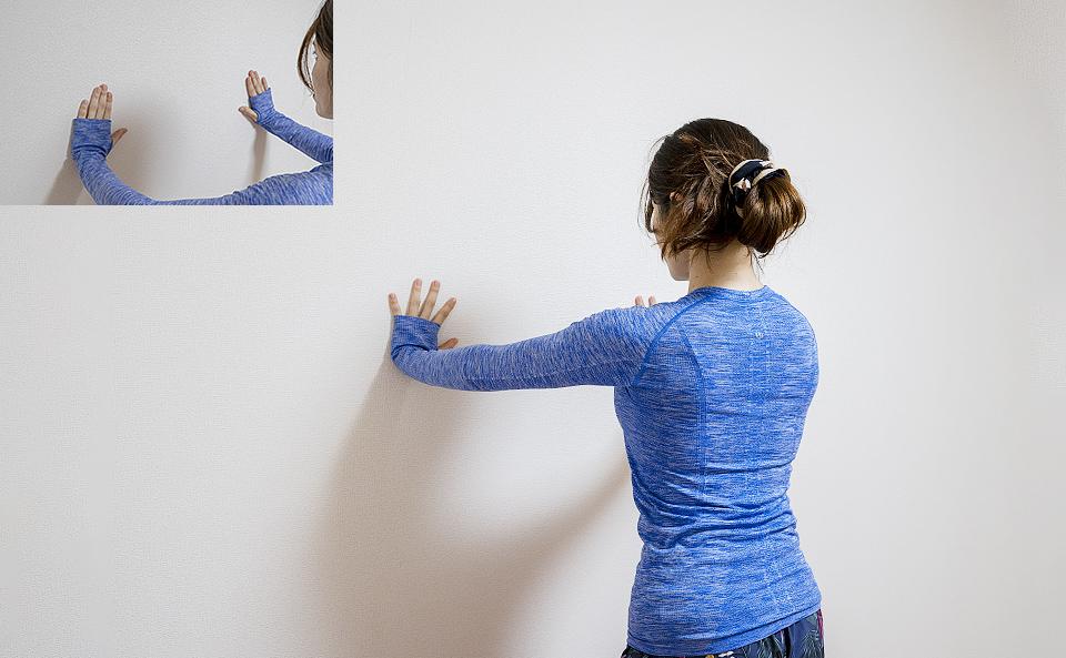 カラダがやや前傾するようにして壁に手をつく